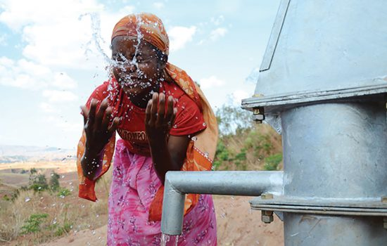 woman washes face with clean water from Rotary and WaterAid