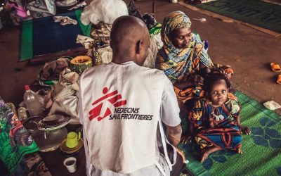 Medecins Sans Frontieres volunteer health worker supports mother and children