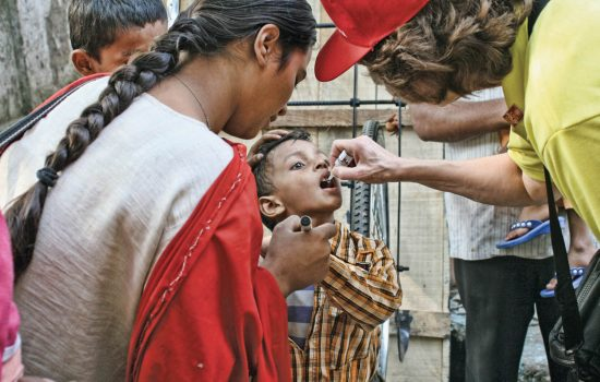 Rotary member delivers polio immunisation to child in India
