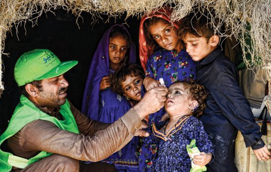 Volunteer delivers polio vaccination to child in Pakistan