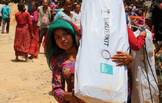 Woman carries disaster relief items supplied by charity ShelterBox