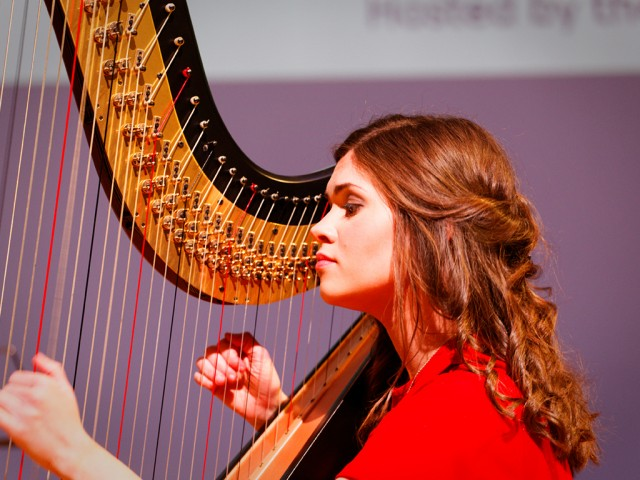 Young Musician plays out well harp