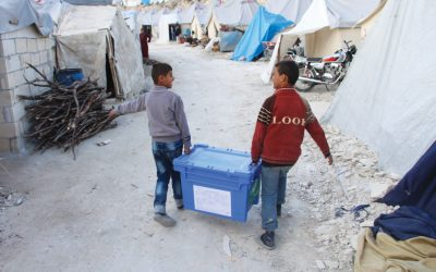Two boys carry Aquabox in refugee camp