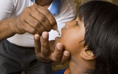 Rotary member administers polio vaccine to child in Nepal our causes fighting disease