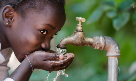 young girl drinks clean water from tap rotary foundation