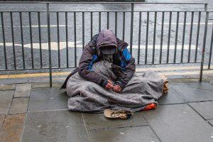 homeless man sits on street in edinburgh