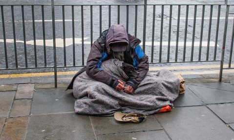 homeless man sits on street in edinburgh