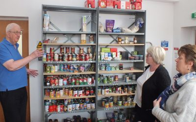 rotary funded foodbank with volunteers and stocked shelves ready for donation