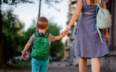 mother and young son walking to school backpack