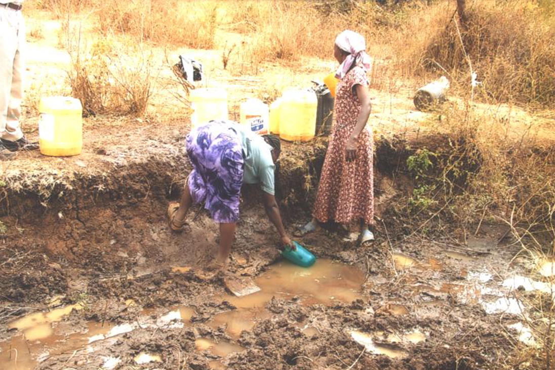 Two Women collecting dirty water before a clean alternative was provided